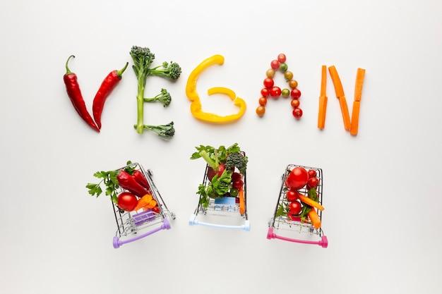 Vegan belettering met kleine winkelwagentjes Gratis Foto