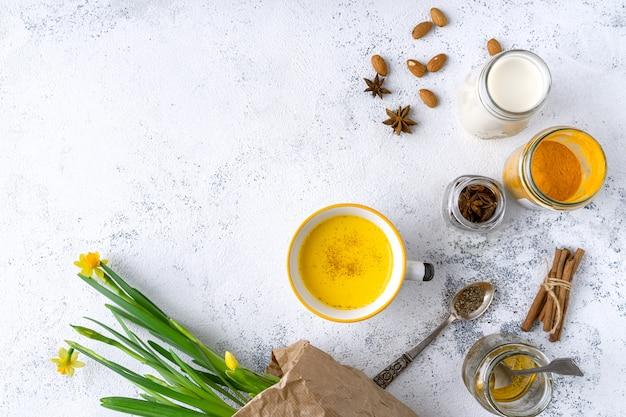 Vegan kurkuma latte in een mok, amandelmelk, honing, kruiden, boeket gele duffodils, bovenaanzicht Premium Foto