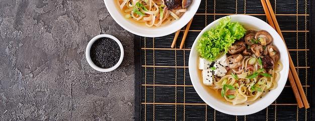 Vegan noedelsoep met tofu kaas, shiitake champignons en sla in witte kom. aziatisch eten. bovenaanzicht. plat liggen Premium Foto