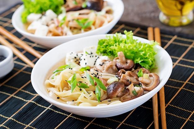 Vegan noedelsoep met tofu kaas, shiitake champignons en sla in witte kom. aziatisch eten. Premium Foto