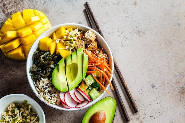 Vegan poke bowl met avocado, tofu, rijst, zeewier, wortelen en mango, bovenaanzicht. veganistisch eten concept. Premium Foto