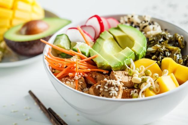 Vegan poke bowl met avocado, tofu, rijst, zeewier, wortels en mango. veganistisch eten concept. Premium Foto