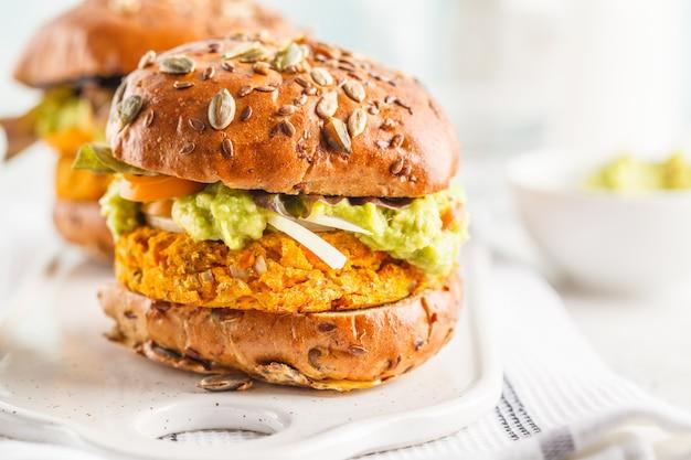 Veganistische bataat (of pompoen) burgers op witte achtergrond. vegetarische hamburgers, avocado, groenten en broodjes. Premium Foto