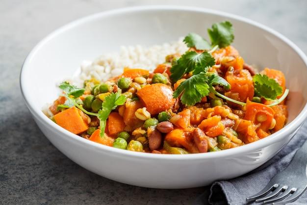 Veganistische curry met rijst in witte kom. curry met zoete aardappel, erwten en bonen in een bord met rijst. Premium Foto