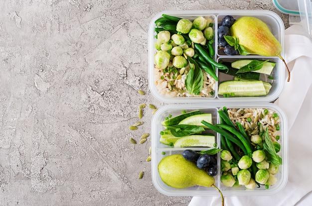 Veganistische groene maaltijdbereidingscontainers met rijst, sperziebonen, spruitjes, komkommer en fruit. diner in lunchbox. bovenaanzicht. plat liggen Gratis Foto