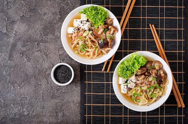 Veganistische noedelsoep met tahoe, shiitake-champignons en sla in witte kom. aziatisch eten. bovenaanzicht plat leggen Premium Foto