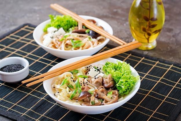 Veganistische noedelsoep met tahoe, shiitake-champignons en sla in witte kom. aziatisch eten. Premium Foto
