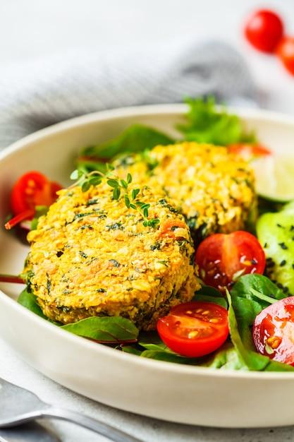 Veganistische pompoen en quinoa koteletten met salade in een witte plaat. Premium Foto