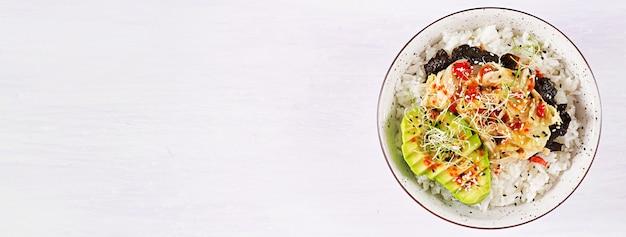 Veganistische salade met rijst, ingelegde kimchi-kool, avocado, nori en sesam op kom. Gratis Foto