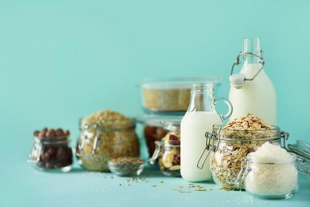 Veganistische vervangende zuivelmelk. glasflessen met niet-zuivelmelk en ingrediënten over blauwe achtergrond met exemplaarruimte. Premium Foto