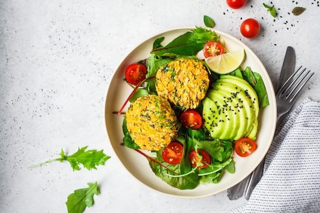 Veganistpompoen en quinoakoteletten met salade in een witte plaat, hoogste mening. Premium Foto