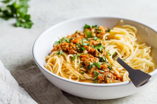 Vegetarische linzen bolognese pasta met peterselie in witte schotel. Premium Foto