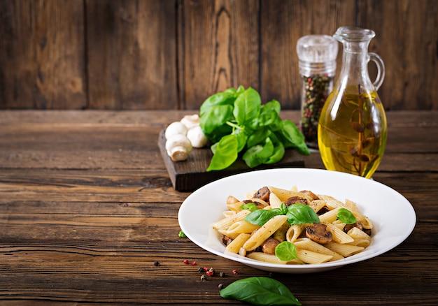 Vegetarische plantaardige pasta penne met champignons in witte kom op houten tafel. veganistisch eten. Gratis Foto