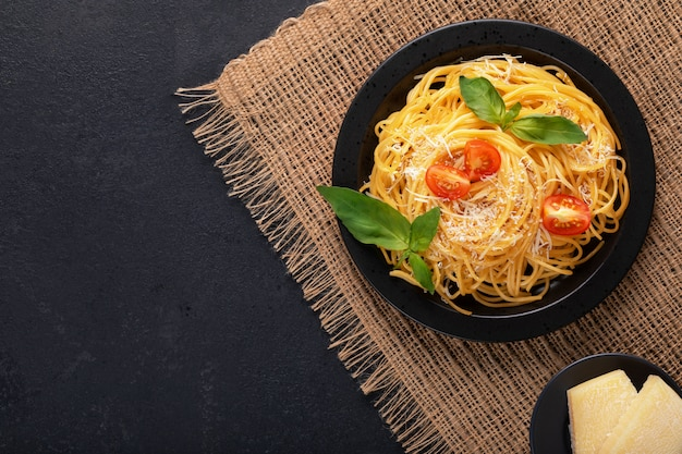 Vegetarische plantaardige smakelijke klassieke italiaanse spaghetti pasta met basilicum, tomaat en parmezaanse kaas op zwarte plaat op een donkere tafel. bovenaanzicht, horizontaal. Premium Foto
