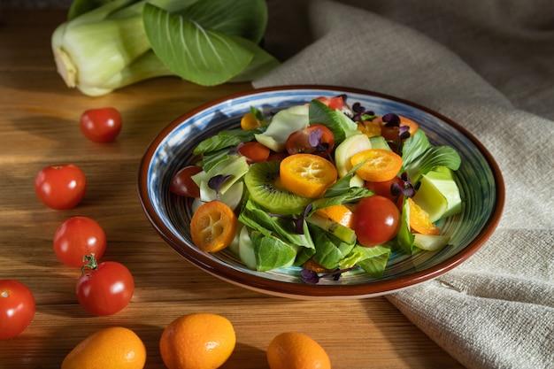 Vegetarische salade van pac choi kool, kiwi, tomaten, kumquat, microgroene spruiten op een houten oppervlak. zijaanzicht, close-up, hard licht. Premium Foto