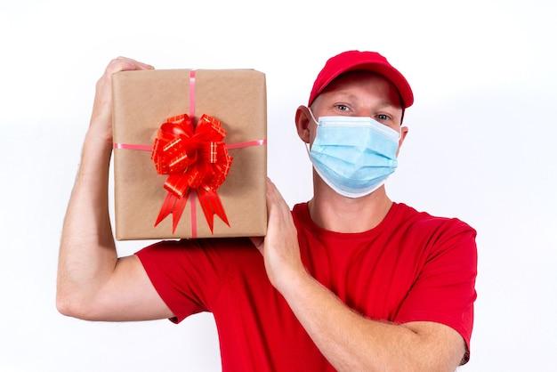 Veilige bezorging van geschenken voor vakanties. een koerier in rood uniform en beschermend medisch masker houdt doos vast Premium Foto