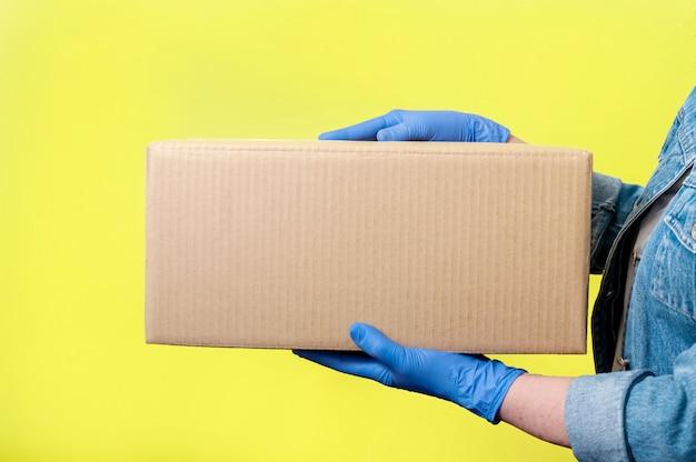 Veilige levering. de close-upvrouw dient handschoenen met kartondoos in. anti-coronavirus concept. mock up. Premium Foto