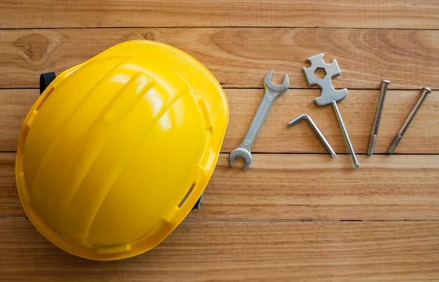 Veiligheidshelm en hulpmiddelen op houten bord van bovenaanzicht Premium Foto