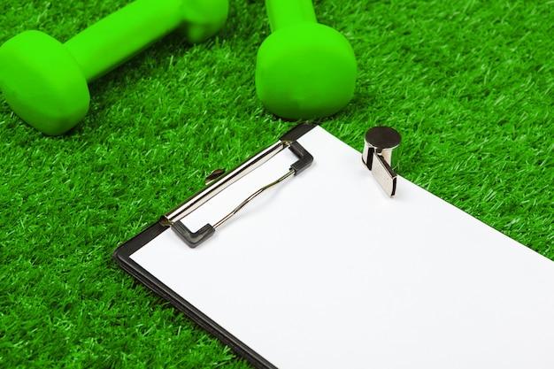 Vel papier en sportartikelen op gras close-up Premium Foto