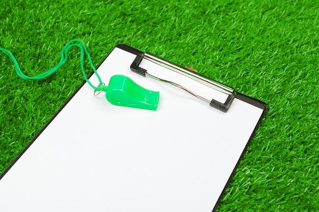 Vel papier en sportuitrusting op gras close-up Premium Foto