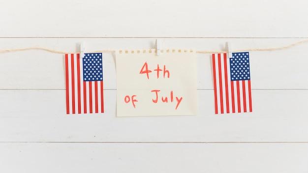 Vel papier met tekst op 4 juli en kleine amerikaanse vlag Gratis Foto
