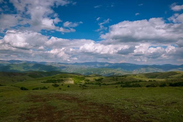 Veld bedekt met het gras omgeven door heuvels bedekt met bossen onder een bewolkte hemel en zonlicht Gratis Foto