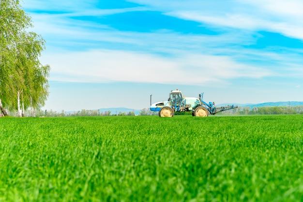 Veld met gras voor vee en tractor bemesten Premium Foto