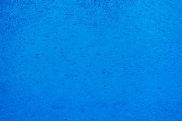 Vele dalingen van water die golven maken wanneer het vallen tijdens een regen op blauw water, blauwe waterachtergrond. Premium Foto