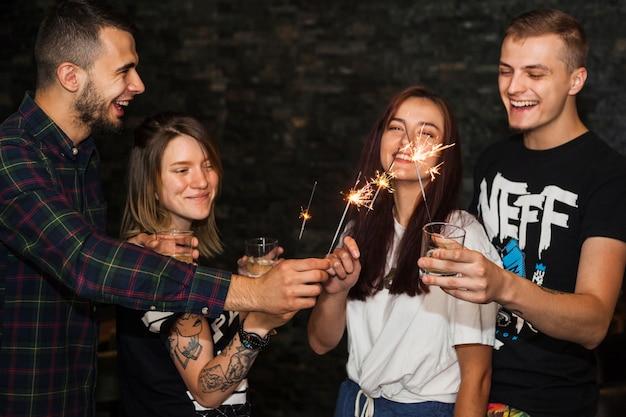 Vele gelukkige vrienden die dranken houden die fonkelen aansteken Gratis Foto