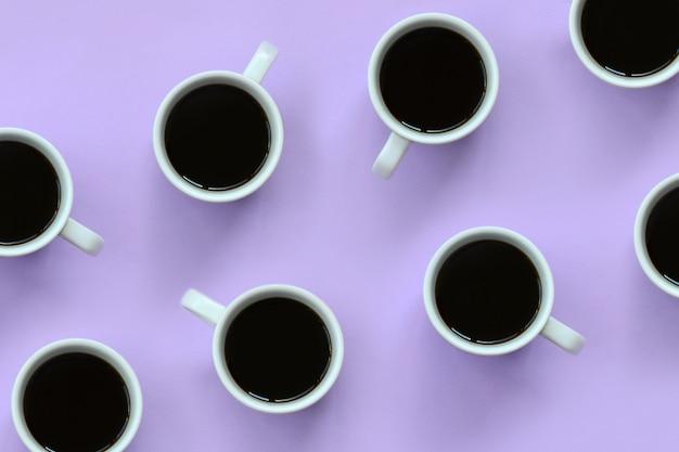 Vele kleine witte koffiekoppen op textuurachtergrond van de violette kleur van de manierpastelkleur Premium Foto