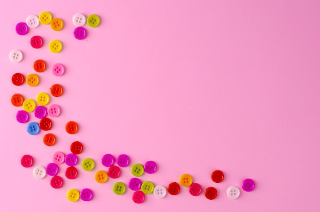 Vele kleurrijke knopen op roze achtergrond. copyspace Premium Foto