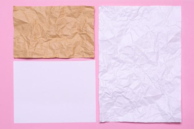 Vellen papier op een roze achtergrond. textuur van verfrommeld papier van verschillende grootte Premium Foto