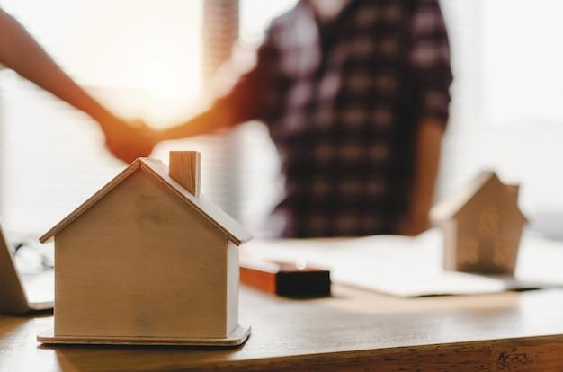 Vennootschap. houten huis model op werkplek bureau Premium Foto