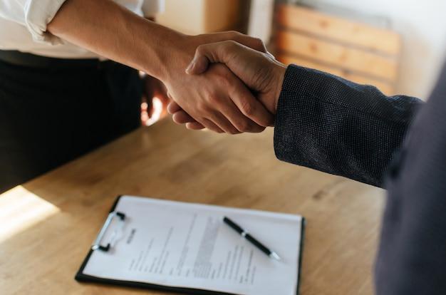 Vennootschap. twee mensen uit het bedrijfsleven handdruk na zakelijke ondertekening contract in het kantoor van de vergaderzaal Premium Foto
