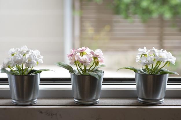 Vensterbank met drie bloempotten op een onscherpe achtergrond Gratis Foto