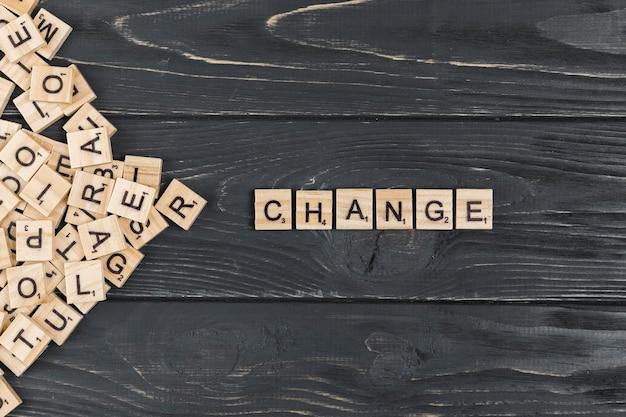 Verander woord op houten achtergrond Gratis Foto