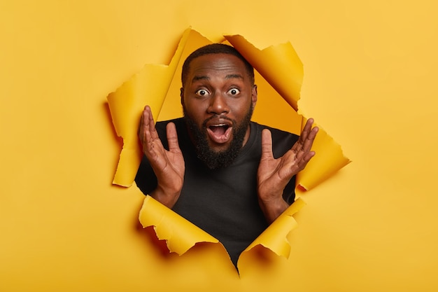 Verbaasd emotionele afro-amerikaanse man steekt zijn handen omhoog, staart met verbaasde uitdrukking, hijgt van verwondering, ongeschoren zijn, handpalmen vastklemt, poseert door gat in geel papier Gratis Foto