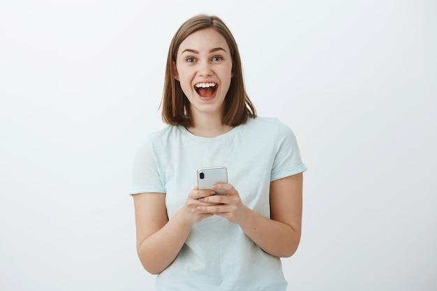Verbaasd en opgewonden aantrekkelijk jong europees vrouwelijk model breed glimlachend van groot nieuws ontvangen via internet met smartphone starend opgewonden en opgetogen poseren tegen een witte muur Gratis Foto