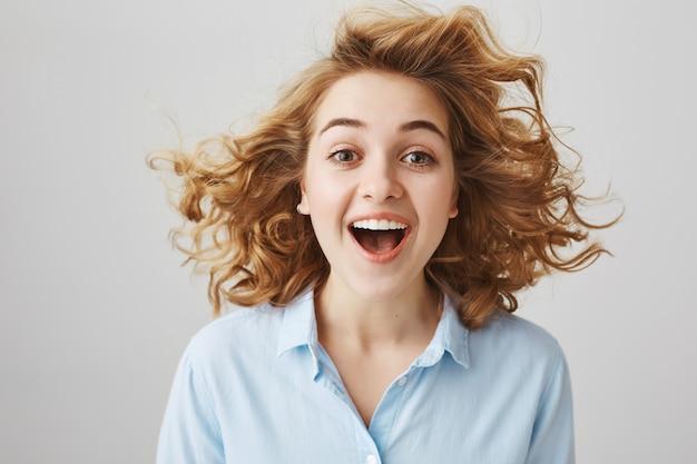 Verbaasd gelukkig meisje met krullend haar dat in de lucht zweeft Gratis Foto