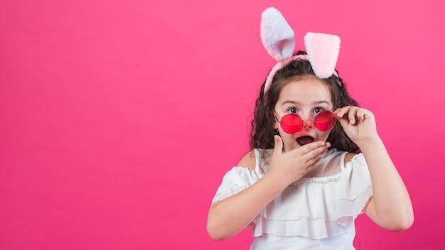 Verbaasd meisje in konijnenoren Gratis Foto