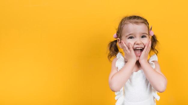 Verbaasd meisje op gele achtergrond Gratis Foto