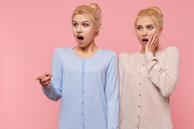 Verbaasd mooie jonge blonde tweeling met wijd open mond geïsoleerd over roze achtergrond wees naar iets geschokt. Gratis Foto