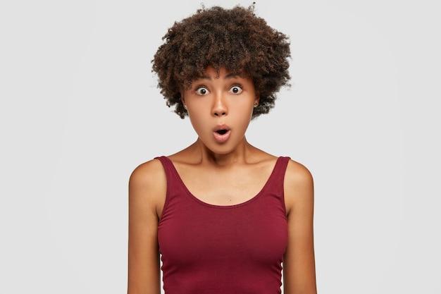 Verbaasd mooie jonge vrouw heeft afro-kapsel, heeft een gezonde donkere huid Gratis Foto