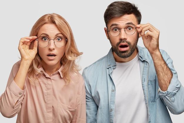 Verbaasd mooie vrouw en zijn mannelijke partner, blikken met ogen vol ongeloof, staren door een bril Gratis Foto