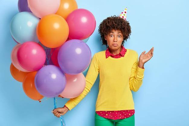 Verbaasd onbewust afro-vrouw staat met gekleurde ballonnen, weet niet waar het feest wordt gehouden Gratis Foto