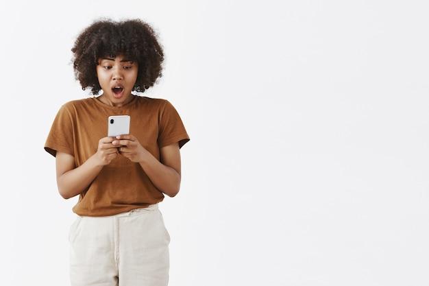 Verbaasd, ontevreden en geschokt afro-amerikaanse tiener vrouw met krullend haar naar adem snakken en kaak laten vallen van teleurstelling kijken naar smartphonescherm Gratis Foto