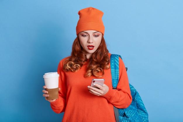 Verbaasd wijfje dat vrijetijdskleding en pet draagt die het slimme telefoonscherm in haar handen met geopende mond bekijkt Premium Foto