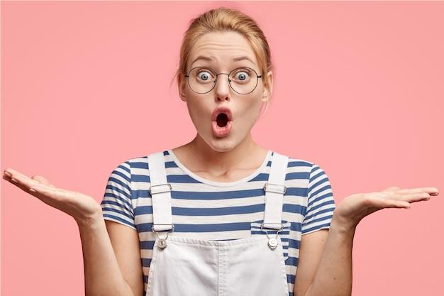 Verbaasde, beschaamde jonge europese vrouw haalt verbijsterd haar schouders op, heeft een verbijsterde uitdrukking, opent mond wijd Gratis Foto