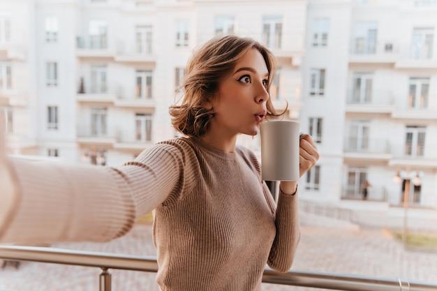 Verbaasde blanke dame in stijlvolle trui genieten van thee. charmant krullend vrouwelijk model kopje koffie houden en selfie maken op balkon. Gratis Foto