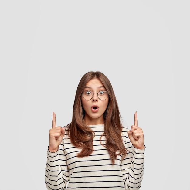 Verbaasde blanke jonge vrouw met een verbaasde verbaasde uitdrukking, steekt wijsvingers op en wijst naar boven Gratis Foto
